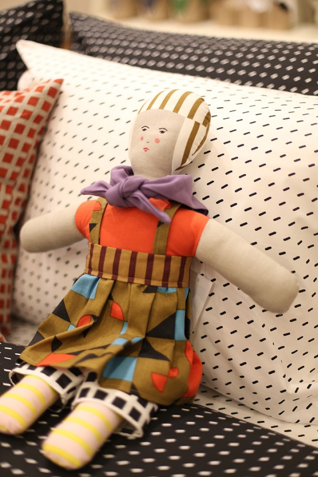 A doll made from scrap fabric rests on a bed